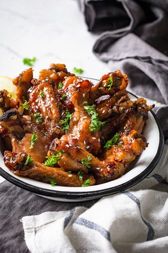 Teriyaki chicken wings in white bowl garnished with sesame seeds, chopped parsley and lemon wedge on marble table. Side view, toned, vertical