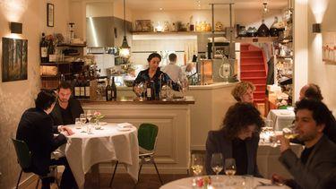 tafels vol gasten in restaurant