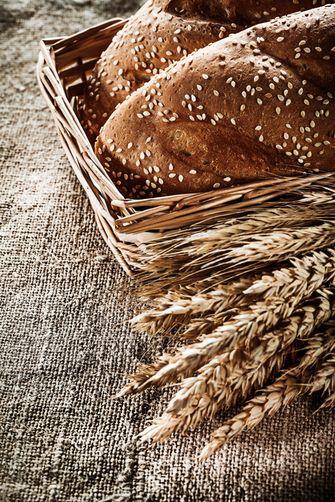 Wicker basket breadstick rye ears on sacking background.