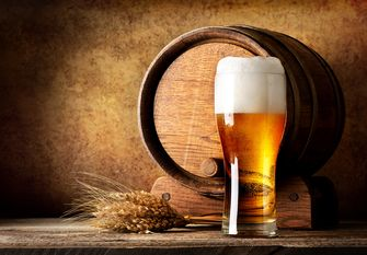 Wooden barrel and beer with wheat on a wooden table