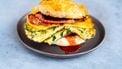 Breakfast sandwich op een scone met spek, kaas en omelet