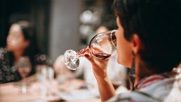 vrouw die deelneemt aan online wijnproeverij