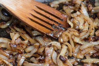 Onions caremelizing in frying pan with wooden cooking spatula
